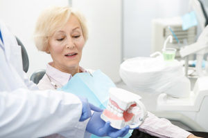 older woman being told about dentures by dentist, general dentistry pasadena tx