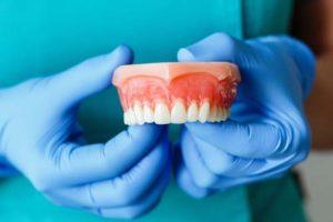 dentist holding a pair of upper dentures