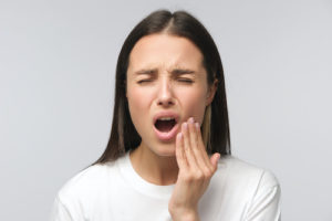 a woman feeling the pain of Impacted Teeth